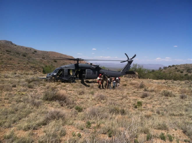 ParaRescuemen from a Tucson Air Force base escort a dazed McNally, along with Diamond Mountain searchers, to safety.